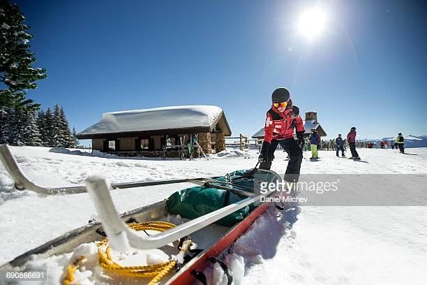 Female ski patrol pulling medical sled.