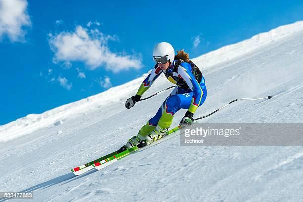 Weibliche Skifahrer in der Straße bergab rennen