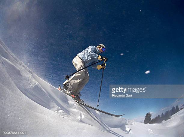 Female skier on slope, side view