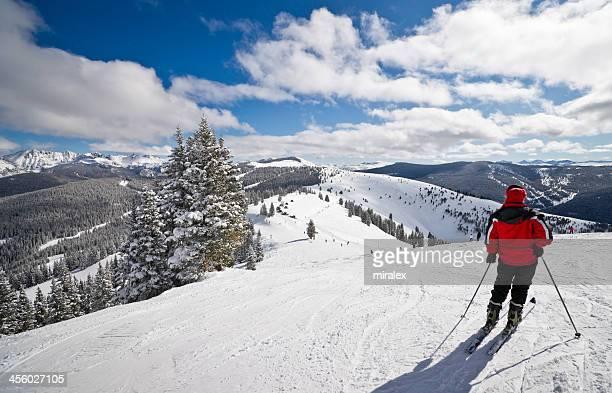 Mulher esquiador pé com montanhas rochosas em segundo plano
