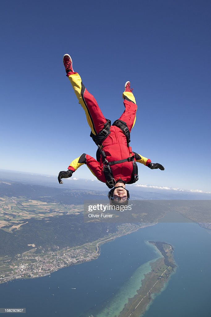 A female skydiver upside down in the sky