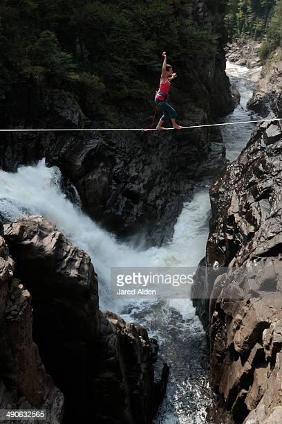 Female slackliner walking a highline over a waterfall