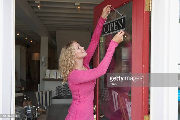 Female small business owner putting up 'open' sign