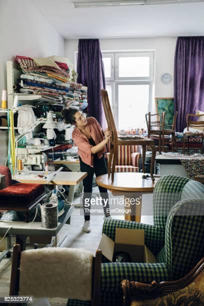 Vrouwelijke kleine ondernemer opknappen stoel In bekleding Studio