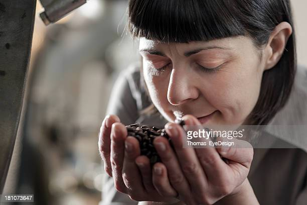 Female small business owner smelling fresh roasted coffee