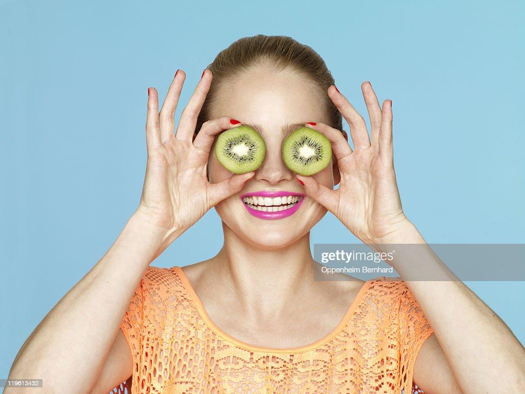 female smiling and holding kiwi halves over eyes