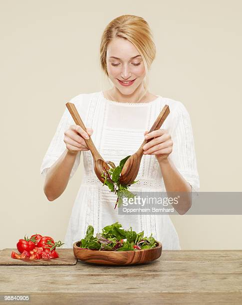 female smiling as she tosses a fresh salad