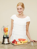 female smiling with ingredients for fruit smoothie