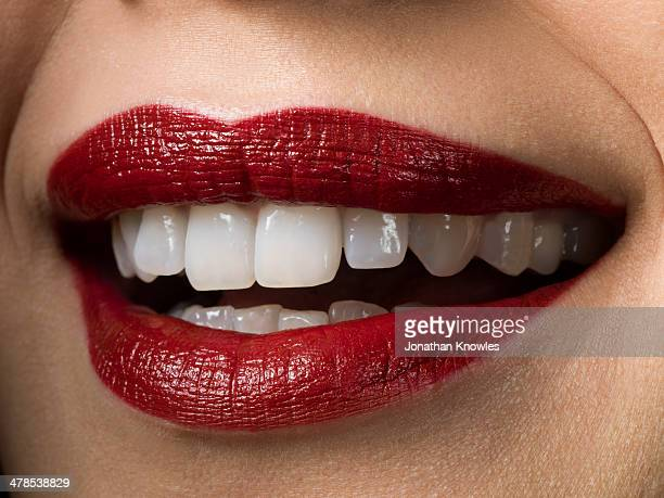 Female smiling with red lipstick on, perfect teeth