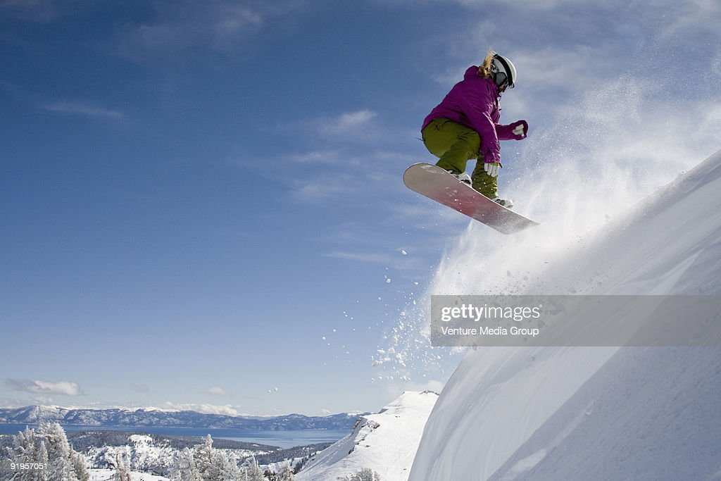 A female snowboarder doing a 540 in the backcountry on a sunny day in, California.