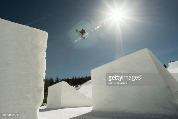 Female Snowboarder getting big air off of a massive jump