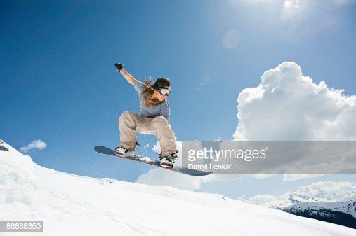 female snowboarder jumping through air : Foto de stock