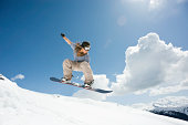 female snowboarder jumping through air