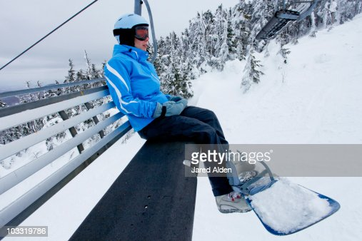 A female snowboarder rides the chair lift in New Hampshire.