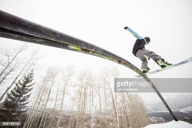 Female Snowboarder Sliding on a Rail Framing an Aspen Grove