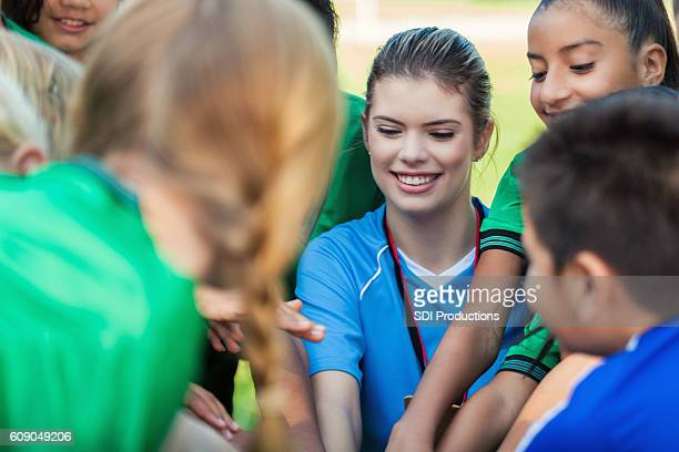 Female soccer coach huddling with diverse soccer teammates