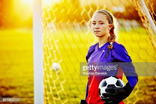 Female soccer goalie holding soccer ball