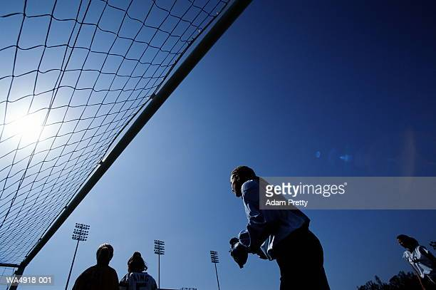Female soccer goalie standing by goal, low angle view