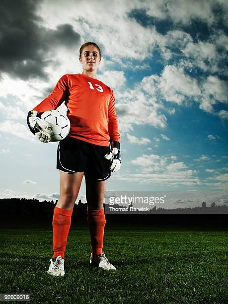 Female soccer goalkeeper standing on field