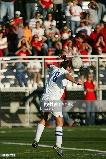 Female Soccer Player Heads Ball with Spectators and Copy Space