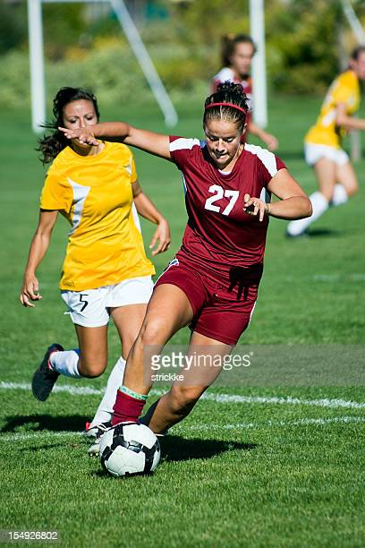 Female Soccer Player in Dark Red Breaks Away From Defender