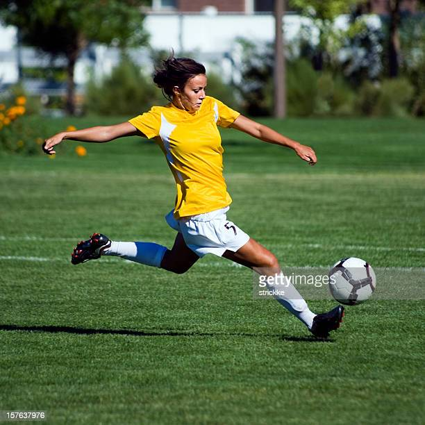 Female Soccer Player in Yellow Jumps to Touch Bouncing Ball