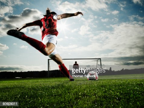Female soccer player kicking ball toward goal