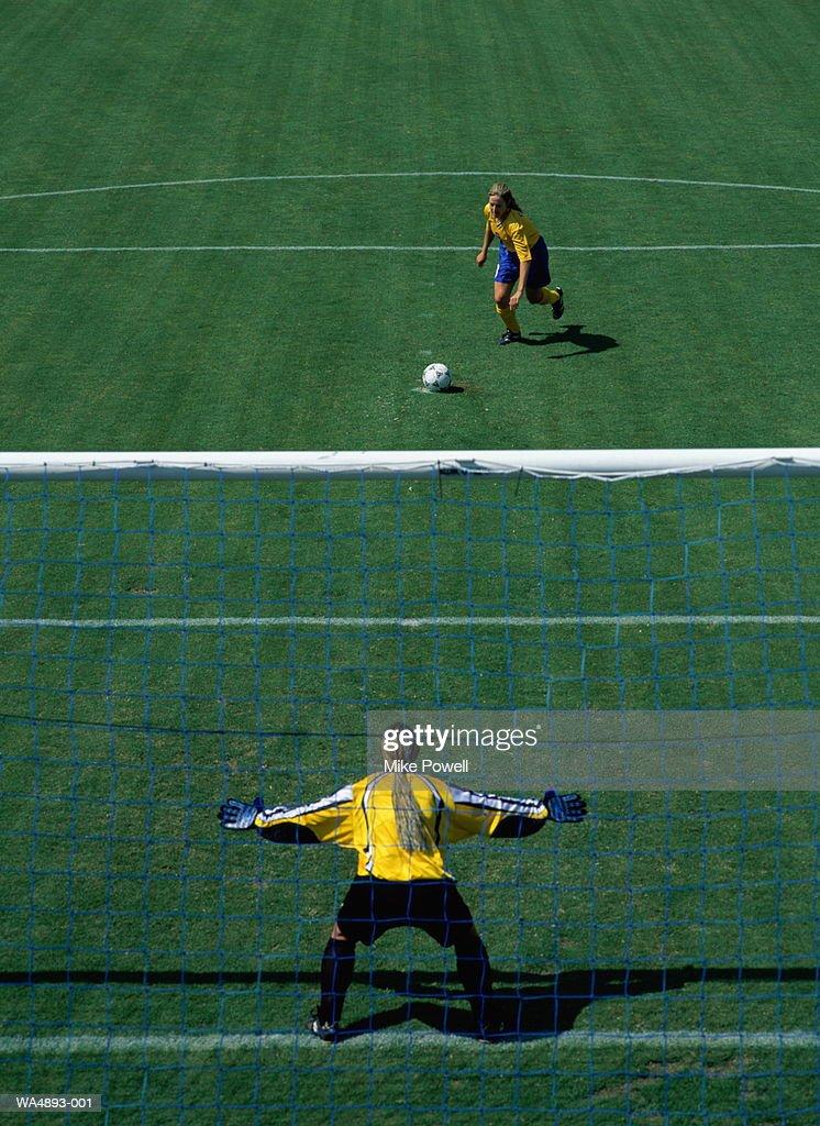 Female soccer player kicking ball towards goal : Stock Photo