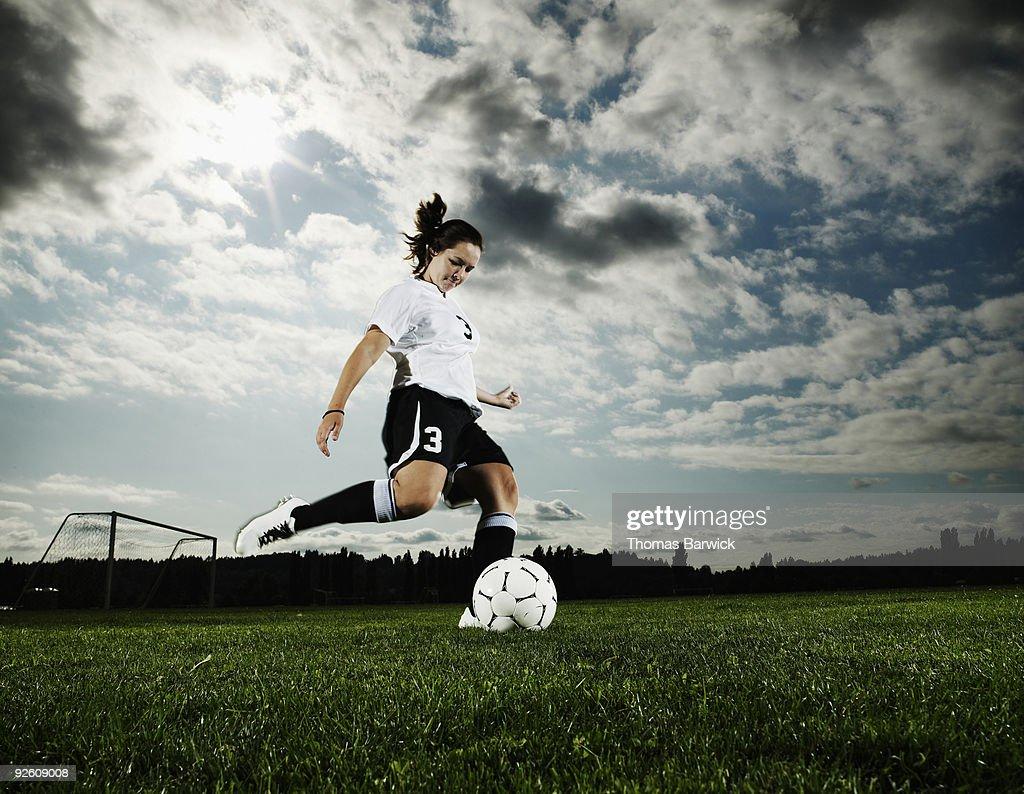 Female soccer player kicking soccer ball : Stock Photo