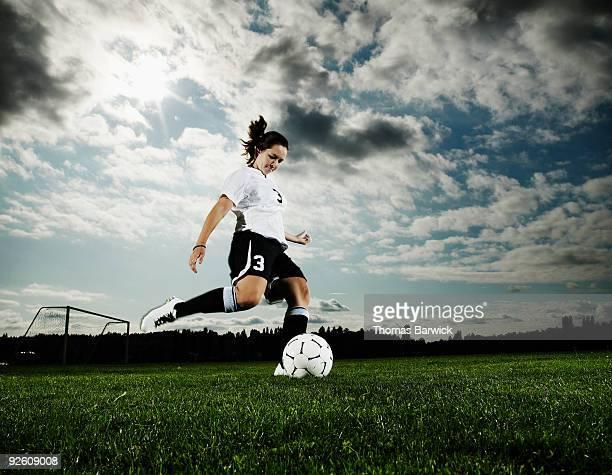 Female soccer player kicking soccer ball