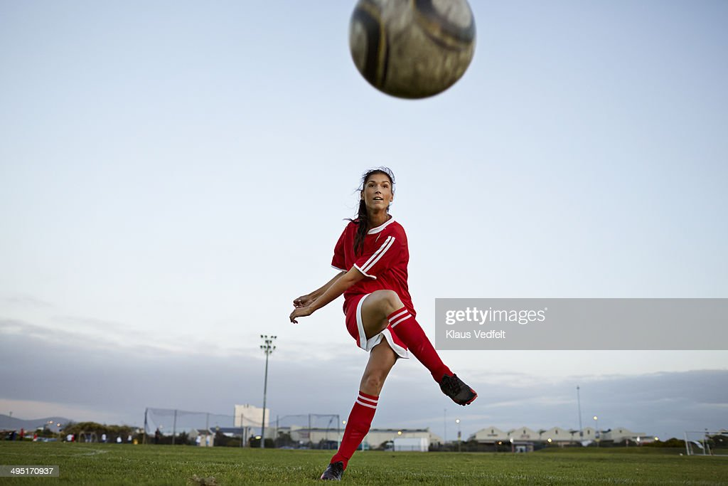 Female soccer player kicking the ball over camera : Stock Photo