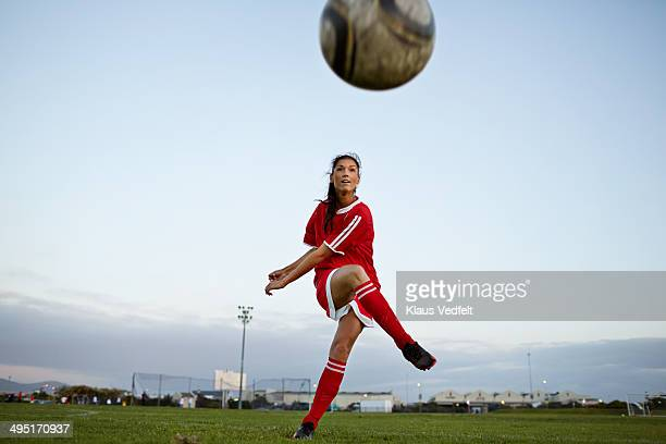 Female soccer player kicking the ball over camera