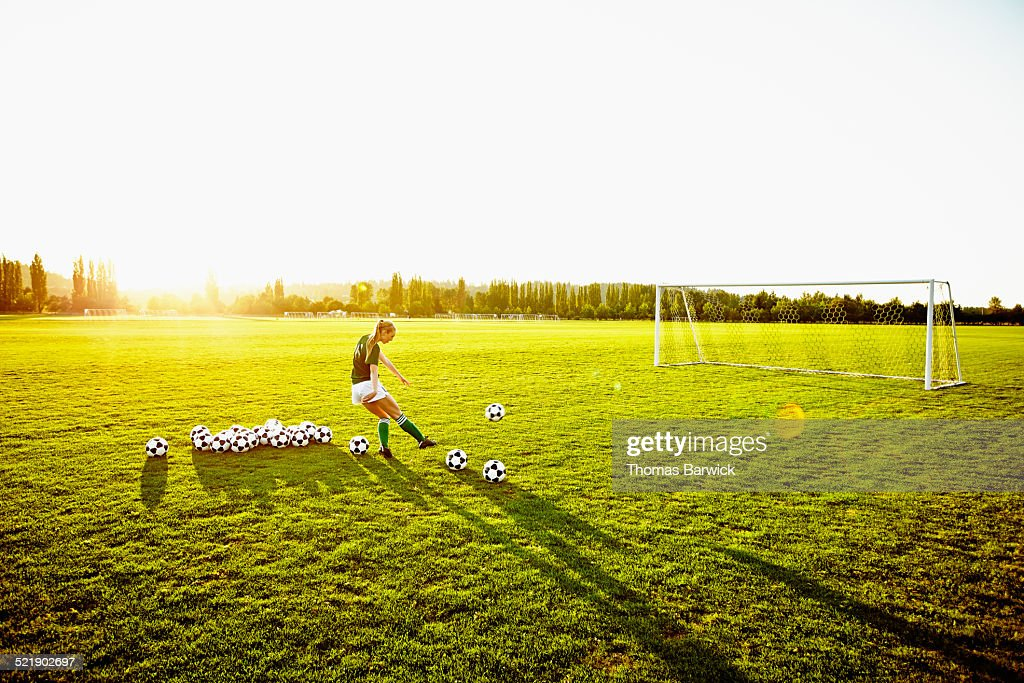 Female soccer player practicing penalty kicks