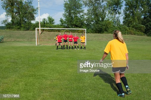 Female soccer player taking free kick : Stock Photo