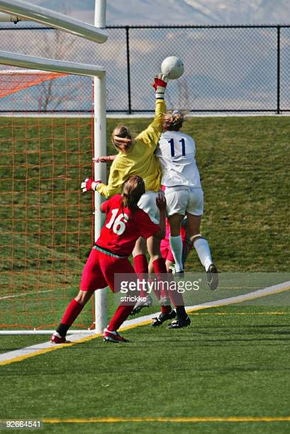 Female Soccer Players Compete for Airborne Ball at Far Post