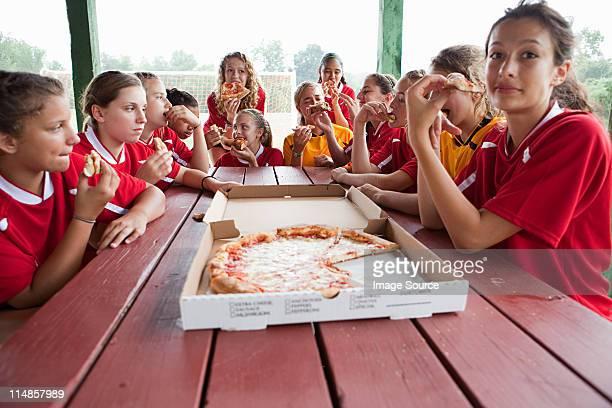Female soccer team having pizza