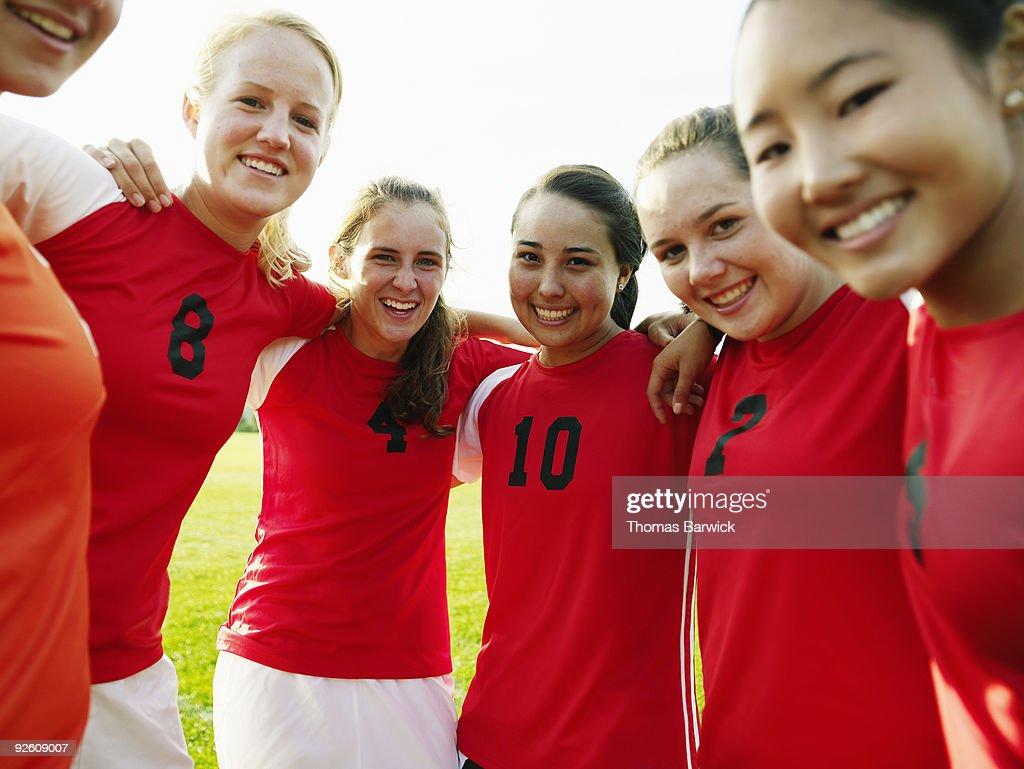 Female soccer team huddled smiling : Stock Photo