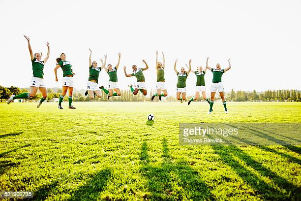 Female soccer team jumping together in mid air