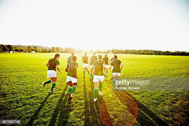 Female soccer teammates warming up on grass field