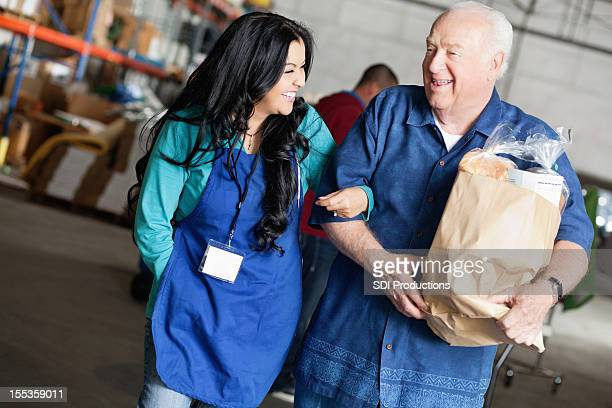 Female social worker laughing with senior man carrying groceries