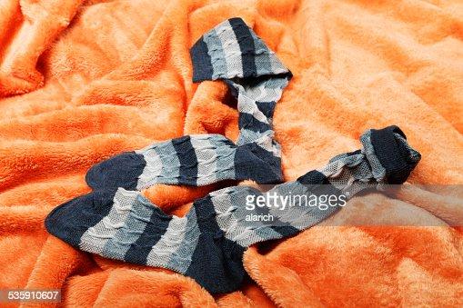 Female socks on an orange blanket : Stock Photo