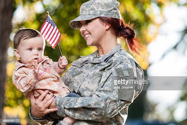 Female Soldier Holding Her Child in Park