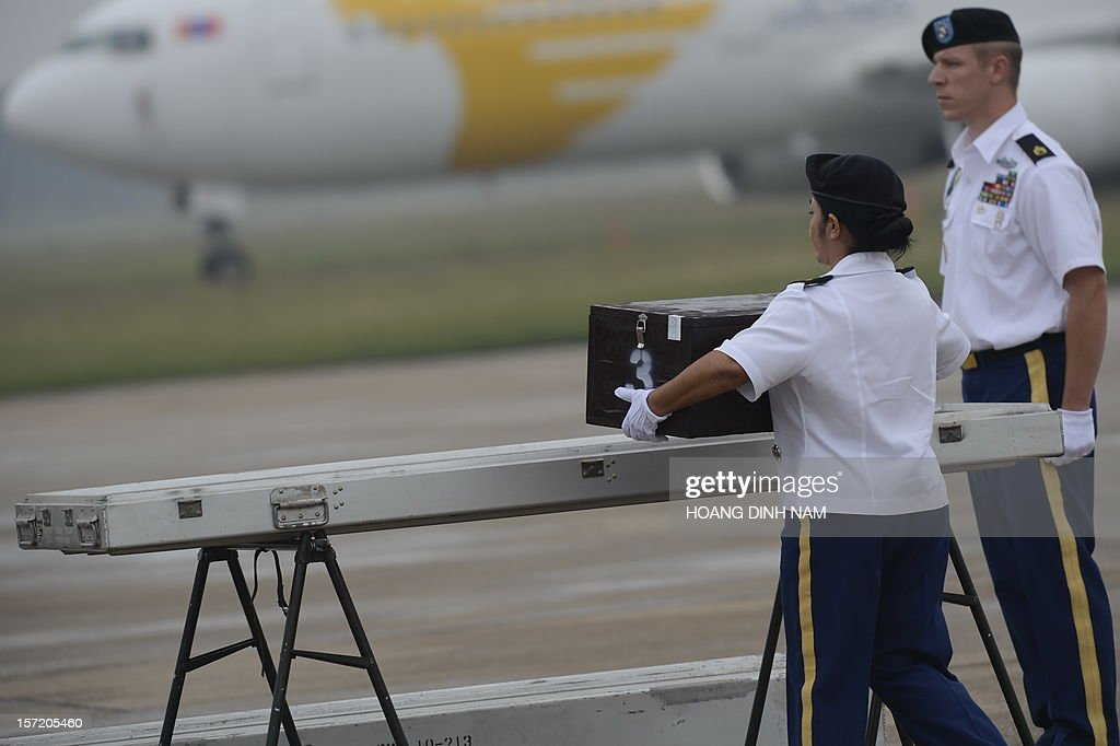 A US female soldier (C) places a wooden box containing what is believed to be remains of a US service man listed as missing in action during the Vietnam war into a casket at a MIA (missing in action) repatriation ceremony held at Hanoi's Noi Bai airport on November 30, 2012. The three remains which were repatriated at this 125th post-war repatriation of US remains from Vietnam were recovered by recent joint MIA research conducted by Vietnamese and US field teams. To date 985 US soldiers from the Vietnam War have been identified since 1973 - 689 from Vietnam, 258 from Laos, 35 from Cambodia and 3 from China, according to a press release from the US embassy in Hanoi. Some 1,661 US soldiers are still unaccounted for from the war, including 1,282 in Vietnam, according to the press release. AFP PHOTO / HOANG DINH Nam