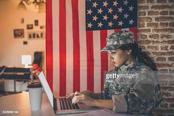 Female soldier using laptop in her modern office