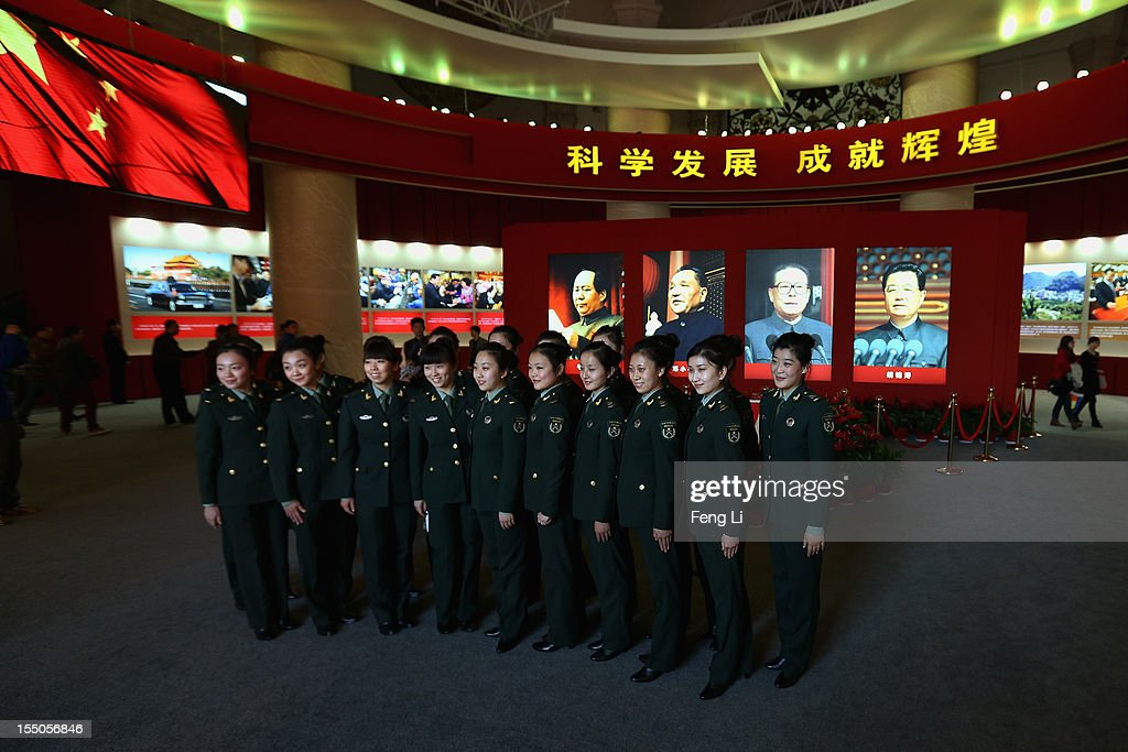 Female soldiers pose for photos in front of the portraits of China's President Hu Jintao and former President Jiang Zemin as visiting an exhibition entitled 'Scientific Development and Splendid Achievements' before the18th National Congress of the Communist Party of China (CPC) on October 31, 2012 in Beijing, China. The exhibition showcases China's progress in political, economic, cultural and ecological spheres over the past decade. The18th National Congress of the Communist Party of China (CPC) is proposed to convene on November 8 in Beijing.