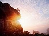 Female solo climber nearing summit of rock