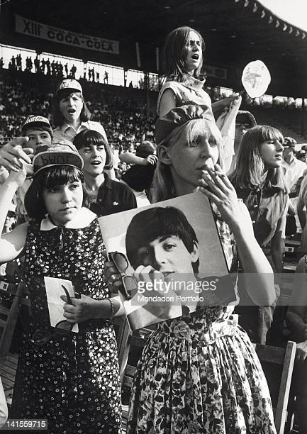 A female spectator with a picture of Paul McCartney at the Beatles concert held at the Velodromo Vigorelli Milan 24th June 1965