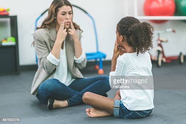 A female speech pathologist is teaching a child patient