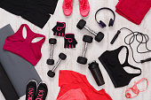 Female sport clothing and equipment top view. Set of fitness outfit and accessories for women, active lifestyle, body care concept
