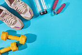 Female sport shoes and equipment on a bright blue background. Active lifestyle, body care concept. Top view. Copy space. Flat lay. Still life